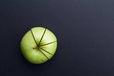 green apple cutting in the shape of pie chart on back board Reklamní fotografie