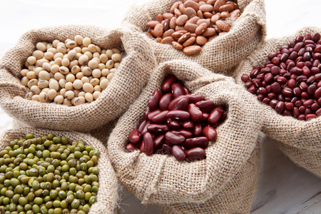 pinto bean: Assortment of beans and lentils in hemp sack on wooden background. green bean, groundnut, soybean, red kidney bean , black bean ,red bean and brown pinto beans
