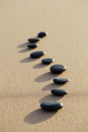 the backbone: set of hot stone on white sand calm beach in backbone shape. selective focus, spa concept