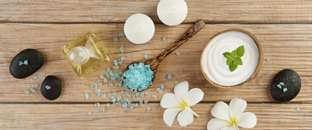 spa setting concept with oil bottle, blue salt sea in spoon, mint on top of white cream in coconut shell, stones, candle and plumeria flowers on wood table