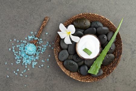 spa concept. slice aloe vera on white cream in coconut shell with salt sea, plumeria, stone background
