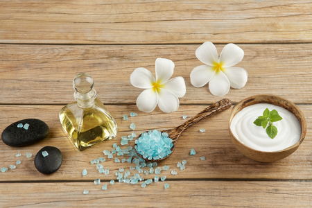 spa flower: spa setting concept with oil bottle, blue salt sea in spoon, mint on top of white cream in coconut shell, stones, candle and plumeria flowers on wood table