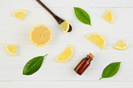Fresh lemons and lemons leaves  with essential oil on rustic wooden background. Fresh lemons and lemon slice with essential oil on white  wooden table with flat lay. Fresh citrus fruit and essential oil background. Reklamní fotografie