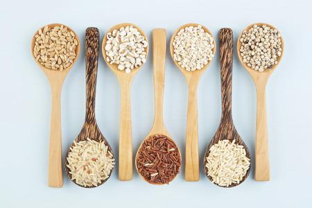 sorgo: Diversas variedades de arroz y cereales integrales en la cuchara en el fondo de la tabla de madera. Trigo, cebada, mijo, avena, arroz, cereales secundarios, sorgo, semilla de loto. Foto de archivo