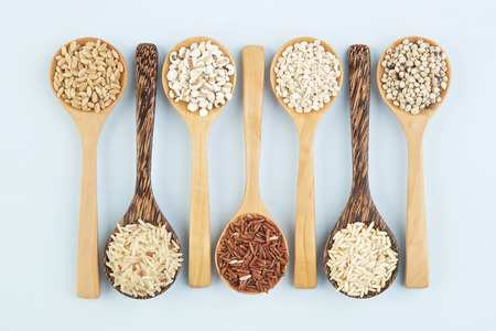 Various varieties of rice and wholegrains in spoon on wooden table background. Wheat, barley, millet, oats, rice, coarse grain, sorghum, lotus seed. Reklamní fotografie