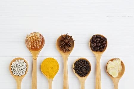 천연 온천 성분. 커피 콩, 나무로되는 숟가락에 고추, 심황, 생강, 꿀, 아니. 상위 뷰에서 흰색 배경에 다양한 나물