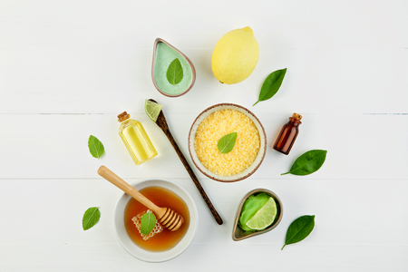 Homemade lemon essential oil, salt bath and fresh honey in the plate with honeycomb, dipper and mints on rustic background from top view. Flat lay good for background and space. Stock Photo