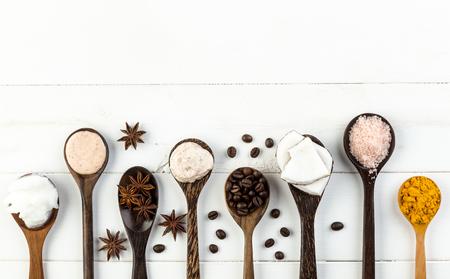 Eigengemaakte kokosnotenproducten op witte houten lijstachtergrond. Olie, scrub, melk, lotion, himalayazout, koffiebonen, anijs en kurkuma vanuit bovenaanzicht. Goed voor ruimte en achtergrond Stockfoto