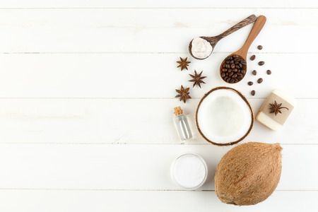 Homemade coconut products on white wooden table background. Oil, scrub, coffe, anise, soap, milk and lotion from top view. Good for space and background