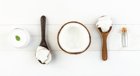Homemade coconut products on white wooden table background. Oil, scrub, milk, lotion and mint from top view. Good for space and background
