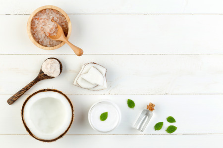 Homemade coconut products on white wooden table background. Oil, scrub, milk, lotion, mint and himalayan salt from top view. Good for space and background Foto de archivo
