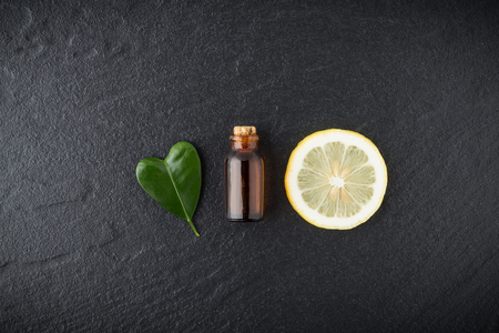 massage symbol: Homemade essential oil concept. Bottle essential oil with slice lemon and leaf in heart shape on black stone background from top view