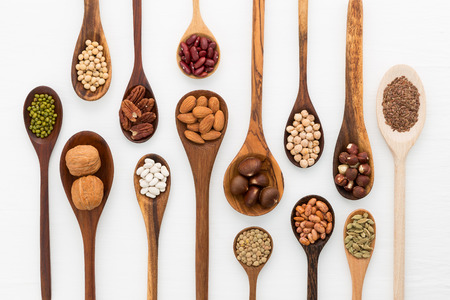 Different kind of beans and lentils in wooden spoon on white wood background. mung bean, groundnut, walnuts, macadamia, almond, soybean, red kidney bean, black bean, sesame, corn, red bean and brown pinto beans