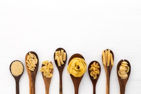 Pasta selectie van penne, gnocci, rigatoni, casarecce, fiorelli, pasta Farfalle, pasta A Riso, Orecchiette Pugliesi, Gnocco Sardo en Farfalle in houten lepels op witte achtergrond Stockfoto