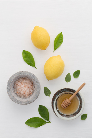 Homemade skincare concept, bath salt, lemon, honey dipper and mint on white wooden background from top view. Good for background and space.
