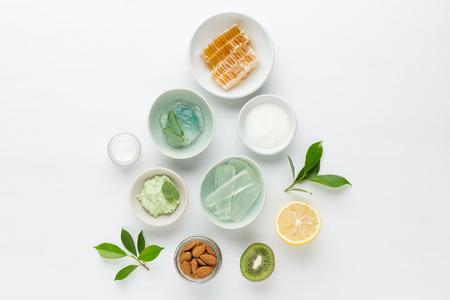 ハーブの皮膚美容とスキンケア製品の化粧品衛生的なクリーム。蜂蜜、レモン、アーモンド、キウイ、キュウリ、アロエベラ、塩、白い背景の上の