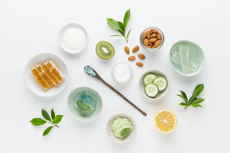 Crème hygiénique cosmétiques à base de plantes médicinales pour produits beauté et de soins de la peau. Miel, citron, amande, kiwi, concombre, aloe vera, sel, yaourts sur fond blanc.