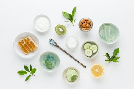 Kruiden dermatologie cosmetische hygiënische crème voor schoonheid en huidverzorgingsproducten. honing, citroen, amandel, kiwi, komkommer, aloë vera, zout, yoghurt op witte achtergrond.