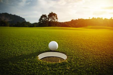 選択と集中。太陽の光とレンズ フレア エフェクトと背景の良い緑の芝生の穴の近く白いゴルフボール