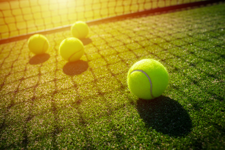 Tennis balls on grass court with sunlight Stock Photo