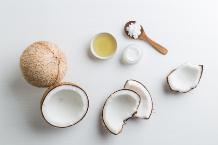 Homemade coconut products on white wooden table background. Oil, scrub, milk and lotion from top view. Good for space and background.