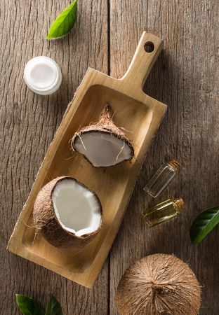 Creative composition coconut half and whole with coconut oil, leaf and coconut products on wooden table background.