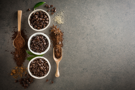 Different varieties of coffee beans with sugar and green leaf on dark vintage background. From top view