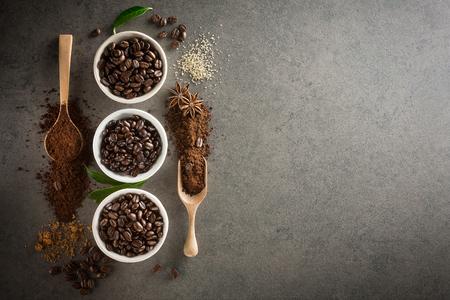 différentes variétés de grains de café avec du sucre et de feuilles vertes sur fond sombre foncé. vue de dessus