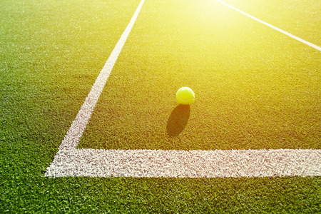soft focus of tennis ball on tennis grass court good for background with sun light Stock Photo