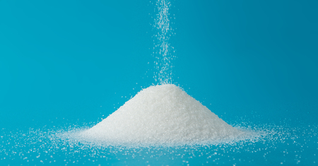 Heap of sugar with pouring on blue background