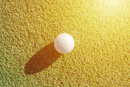 White golf ball on green grass with hard shadow.