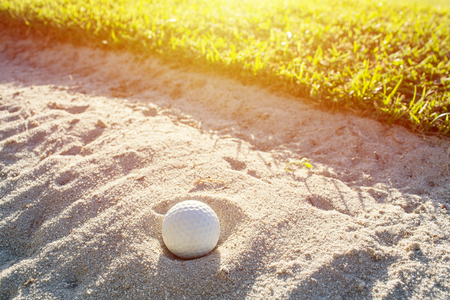 Selective focus of white golf ball on the green field and sand bunker with sunlight.
