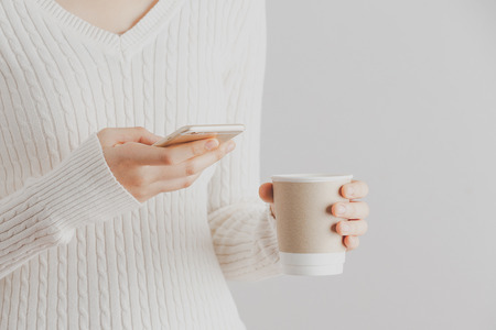 Soft focus young girl hands using smartphone and hold a cup of coffee.