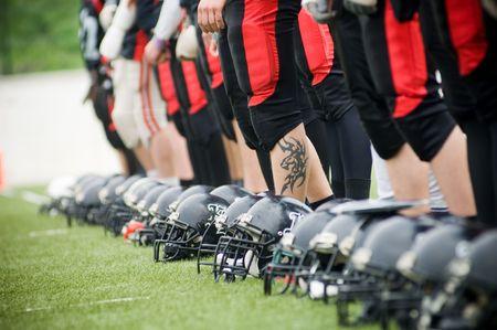 Row of football helmets and feet on grass, selective focus