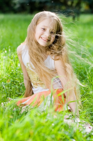 little girl smiling: Little girl in perfect green grass, focus on face Stock Photo