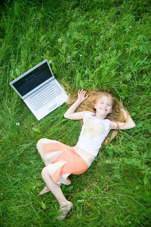 grass skirt: Funny little girl with laptop in green grass