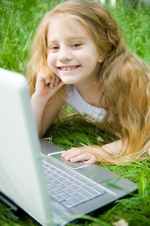 Smiling little girl with laptop in green grass Stock Photo - 3093014