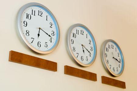 Row of clocks hanging on wall photo