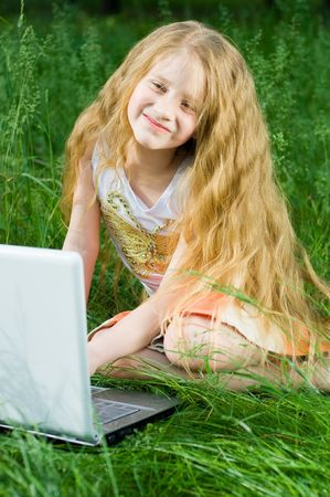 grass skirt: Funny little girl sitting with laptop in green grass