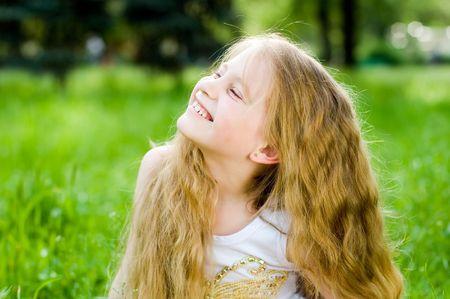 Souriant petite fille en vert herbe