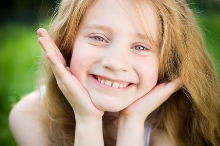 Smiling małą dziewczynką na zewnątrz na zielonej trawie