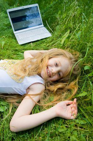 Funny bambina con il computer portatile in verde erba