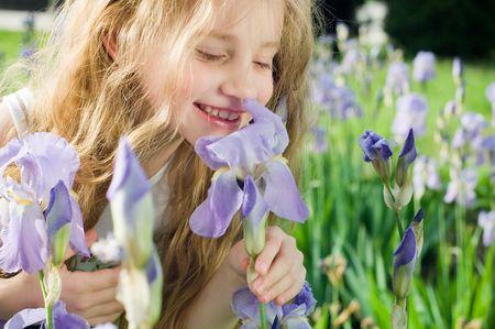 Bambina profumati fiori viola al di fuori  Archivio Fotografico