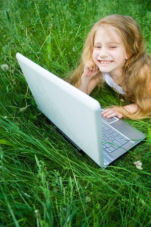 Cute petite fille avec leur ordinateur portable en herbe verte  Banque d'images