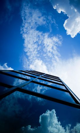 Skyscraper with reflection of clouds in windows photo