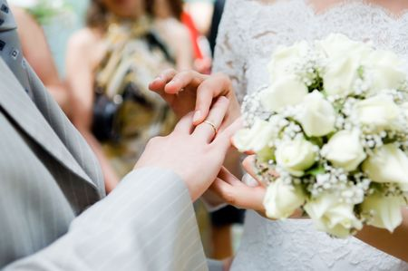 Close-up of young newly-married putting on rings photo
