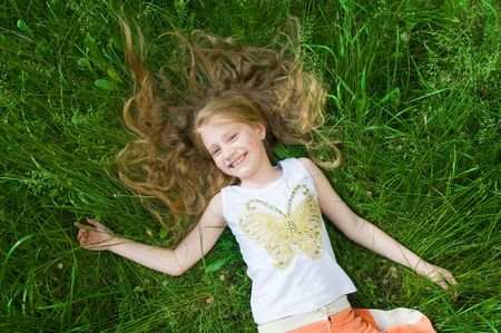 Smiling little girl in green grass, perfect for summer vacation
