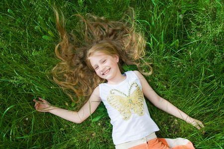 Souriant petite fille dans l'herbe verte, idéale pour les vacances d'été