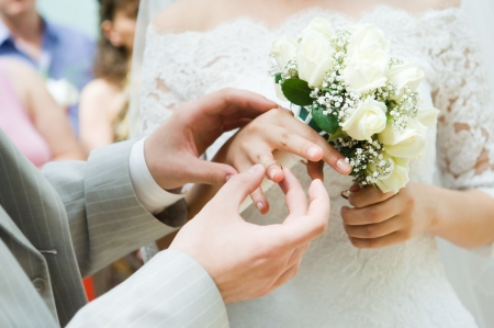 Close-up of young newly-married putting on the rings photo
