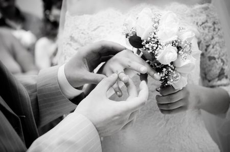 Close-up of young newly-married putting on rings, grayscale  photo
